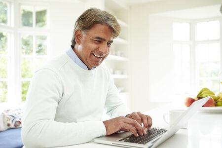 家でノート パソコンを使用してインドの年配の男性
