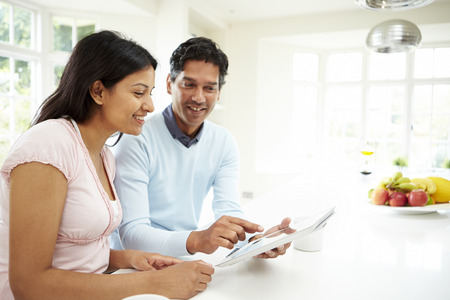 Indian Couple Using Digital Tablet At Home