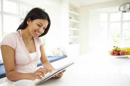 working woman: Indian Woman Using Digital Tablet At Home Stock Photo