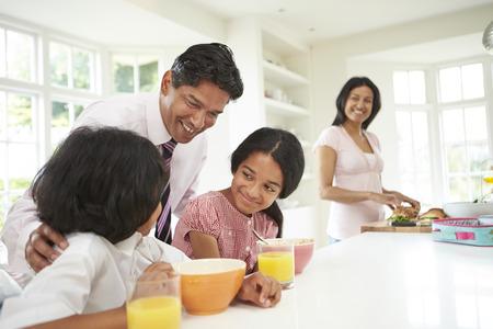 Familie die ontbijt Voordat Vader naar zijn werk Stockfoto
