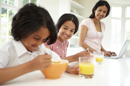 asian bowl: Children Having Breakfast With Mother Before School Stock Photo