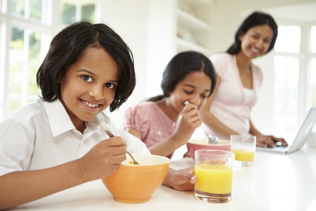 indian happy family: Children Having Breakfast With Mother Before School Stock Photo