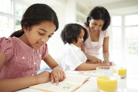 11 year old girl: Mother Helping Children With Homework Stock Photo