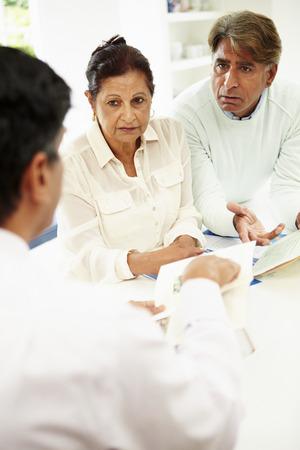 Hogere Indische paarvergadering Met Financieel Adviseur thuis