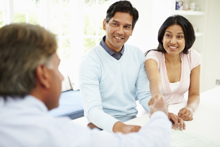 financial advisor: Indian Couple Meeting With Financial Advisor At Home
