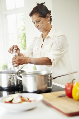 indian cooking: Senior Indian Woman Cooking Meal At Home