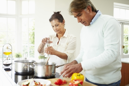 indian cooking: Senior Indian Couple Cooking Meal At Home