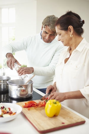 Senior Indian Couple Cooking Meal At Home photo