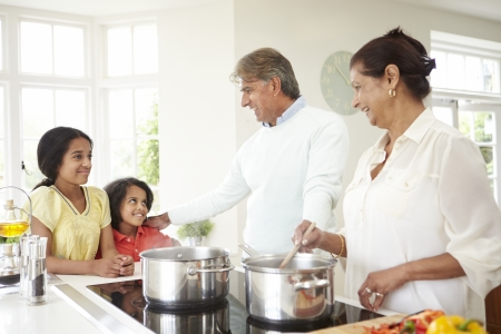 cookers: Grandparents And Grandchildren Cooking Meal At Home