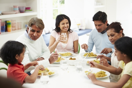 Multi Generation Indian Family Eating Meal At Home photo