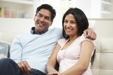 woman couch: Indian Couple Sitting On Sofa Watching TV Together