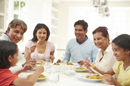 family eating: Multi generacional Indian Comer comida en el hogar