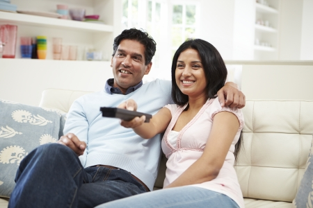 Indian Couple Sitting On Sofa Watching TV Together photo