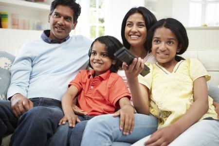 mujer viendo tv: Indian Familia que se sienta en el sof� viendo la televisi�n juntos