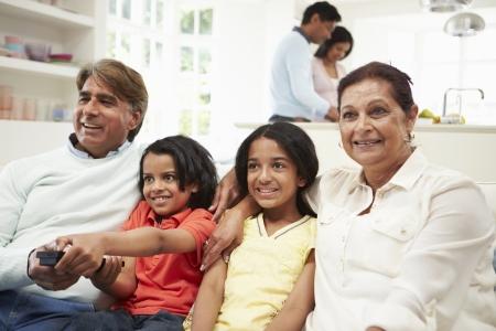 personas mirando: Familia multi-generacional indio sentado en el sofá que ve la TV Foto de archivo