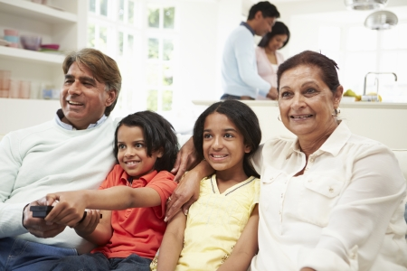 woman watching tv: Multi-Generation Indian Family Sitting On Sofa Watching TV