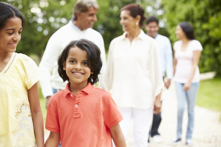 family exercise: Muti-Generation Indian Family Walking In Countryside Stock Photo