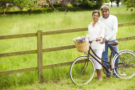 Senior Indian Couple On Cycle Ride In Countryside photo