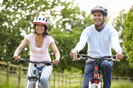 Indian Couple On Cycle Ride In Countryside Stock Photo