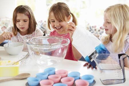 Three Girls Making Cupcakes In Kitchen photo