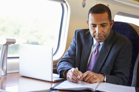 and the horizontal man: Businessman Commuting To Work On Train And Using Laptop