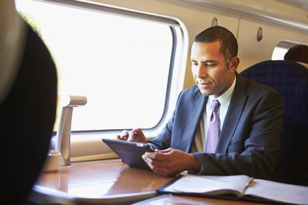 사업가 디지털 태블릿을 사용하여 기차 통근