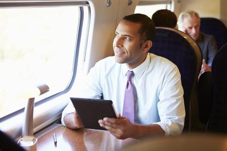 commuting: Businessman Commuting On Train Using Digital Tablet Stock Photo
