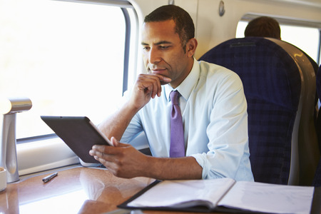 Businessman Commuting On Train Using Digital Tablet Фото со стока