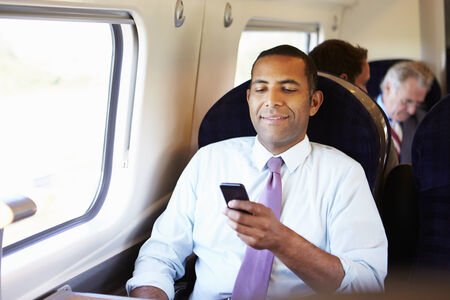mobile: Businessman Commuting To Work On Train Using Mobile Phone Stock Photo