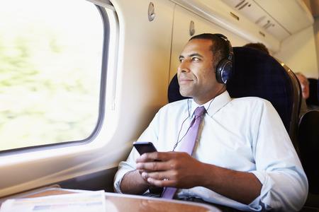 audifonos: El hombre de negocios se relaja en el tren que escucha la m�sica