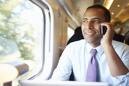 commuting: Businessman Commuting To Work On Train Using Mobile Phone Stock Photo