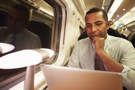 commuting: Businessman Commuting To Work On Train And Using Laptop At Night Stock Photo