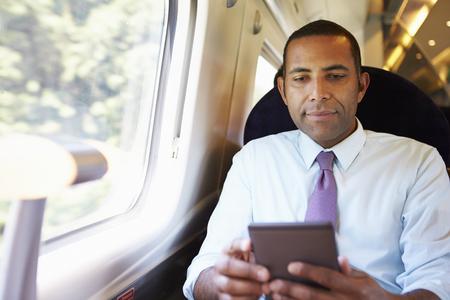 e reading: Businessman Commuting On Train Reading E Book