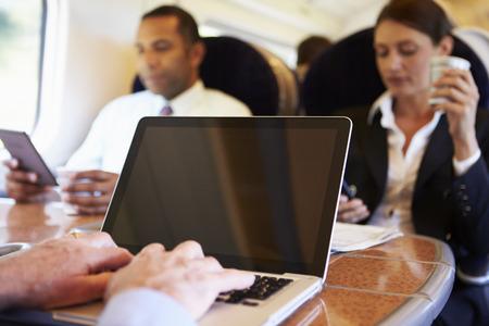 사업가 기차 통근 및 노트북을 사용하는