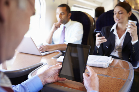 Businesspeople On Train Using Digital Devices photo