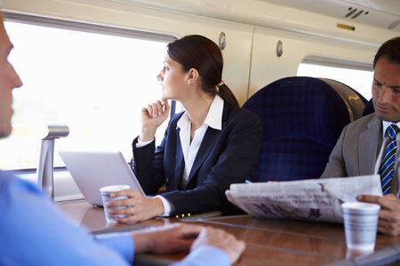 working on computer: Businesswoman Commuting To Work On Train And Using Laptop Stock Photo