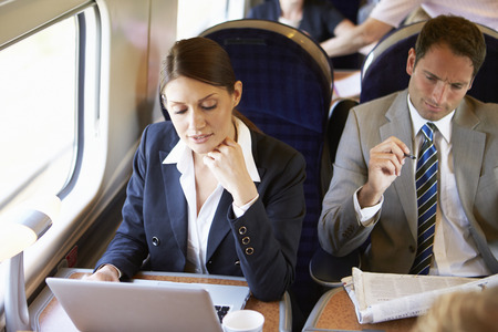 Businesswoman Commuting To Work On Train And Using Laptop Imagens