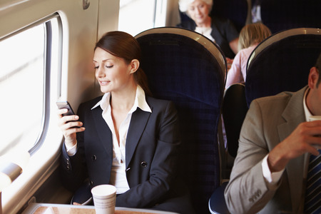 business: Businesswoman Commuting To Work On Train Using Mobile Phone