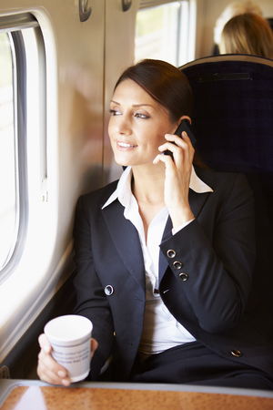 Female Commuter With Coffee On Train Using Mobile Phone  photo