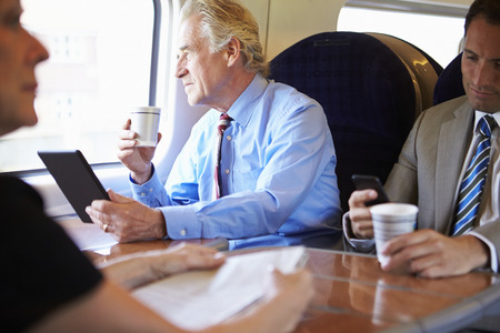 commuters: Businessman Relaxing On Train With Cup Of Coffee