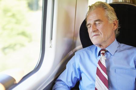Businessman Resting On Train Stock Photo