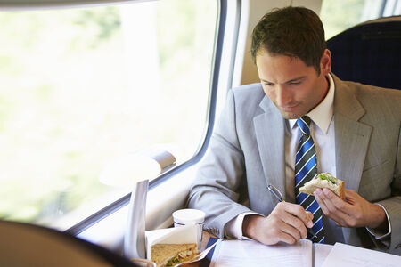 Businessman Eating Sandwich On Train Journey Stock Photo