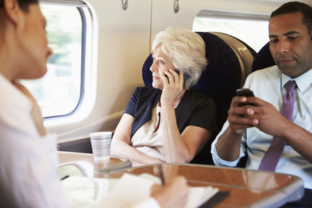 Businesswoman Using Mobile Phone On Busy Commuter Train photo