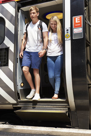 getting together: Young Couple Getting Off Train At Platform