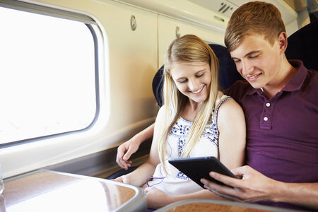 Young Couple Reading E Book On Train Journey photo