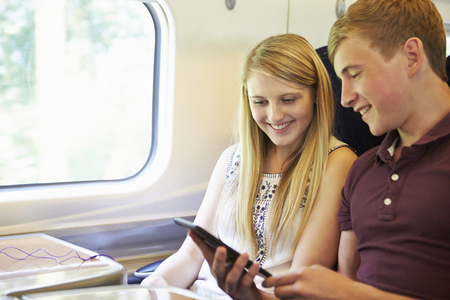 e reading: Young Couple Reading E Book On Train Journey