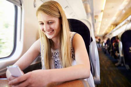 Teenage Girl Using Mobile Phone On Train Journey