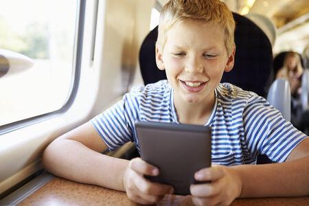 Boy Reading E Book On Train Journey photo
