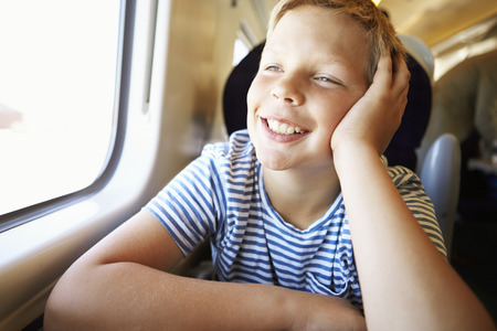 Boy Relaxing On Train Journey Stock Photo