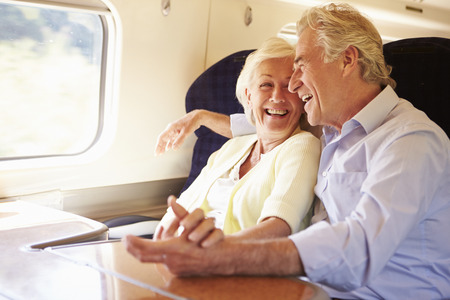 relaxed: Senior Couple Relaxing On Train Journey Stock Photo